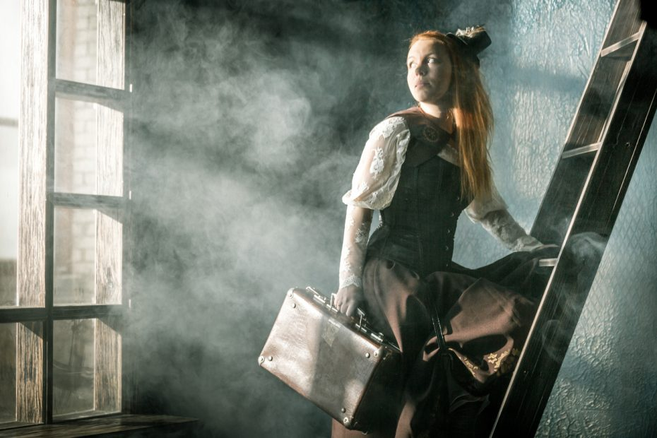 Redhead young woman dressed in steampunk style is standing one foot on a wooden ladder in cloud of steam. She holding a old suitcase in her hand and looking over shoulder on a large window